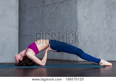 Side view of skinny young yogini standing in yoga backbend pose on mat in studio.