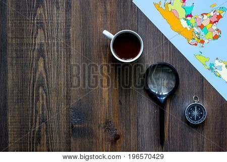 Planning trip. World map and compass on wooden table background top view.