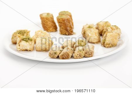 Crunchy Assabeh cashew baklava pieces arranged on a white plate. Dainty sweet dessert morsels made of flaky pastry as served in Middle Eastern cuisine. Closeup studio shot on bright table top.
