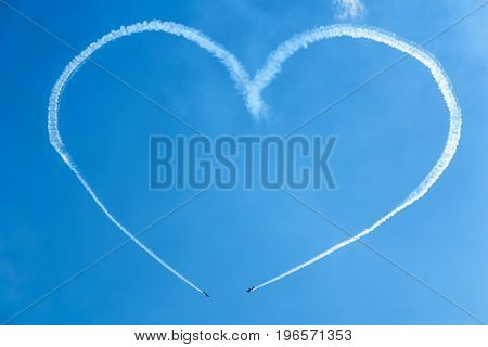 A heart in the blue sky from two skywriting small planes at an air show