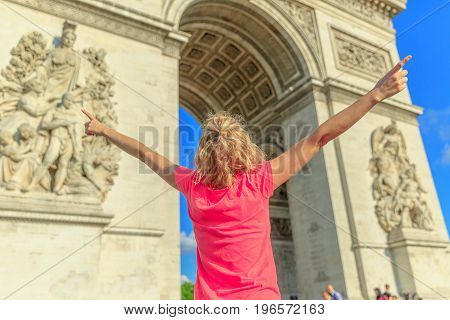 Happy woman with open arms at Arch of triumph. Caucasian lifestyle traveler enjoys at Arc de Triomphe in Paris, France. Holidays in European Capitals. Freedom and travel concept. Blurred background.