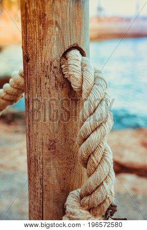 Detail of rope railing of beach walkway old wooden pole blue sea sand in the background seaside vacation tranquility relaxation