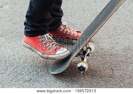 Skater doing flicking trick with skateboard tail. Level up skill. Streetwear style with red sneakers footwear