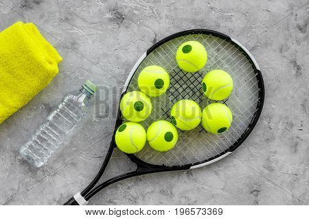 Sport background. Tennis balls and racket on grey background top view.