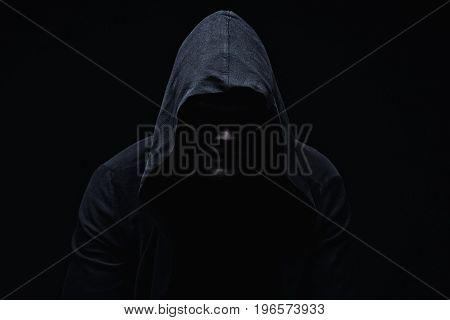 Hooligan young man in hood on black background