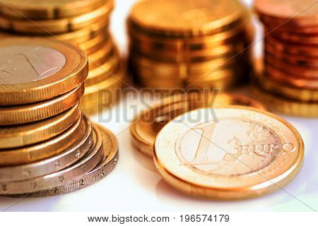 Stack of shiny white and golden Euro coins of different value on white background finances investment stock savings concept warm toning close up
