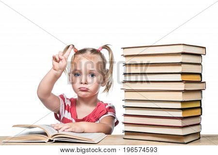 Child is sitting at a desk and studying a book with his index finger up, isolated on a white background