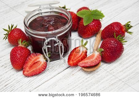 Strawberry jam with fresh strawberries on a wooden table