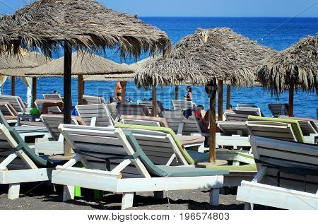 Beach umbrellas and sunbeds at the sea close-up.