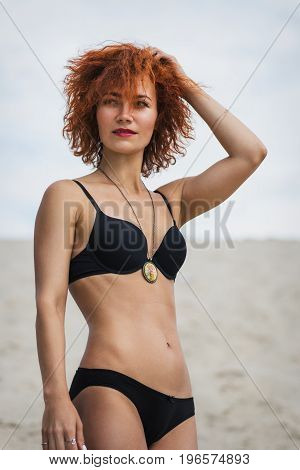 fashion outdoor photo of beautiful sexy girl with red hair and tanned skin wears black bikini and accessories relaxing on summer beach.