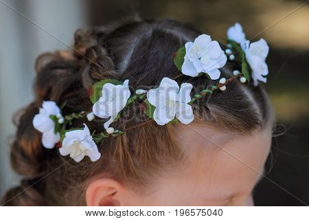 hair wreath - a stylish accessory on the child's head wreath of artificial flowers in the hair of a little girl top view