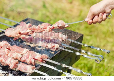Hand puts skewer with pieces of meat for a shish kebab barbeque on outdoors grill with green blurry background.