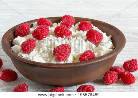 bowl of cottage cheese with fresh ripe raspberry for healthy breakfast. close up