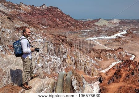 Photographer traveler on foot hiking up the salt mountains in Hormuz Island Hormozgan Province Iran.