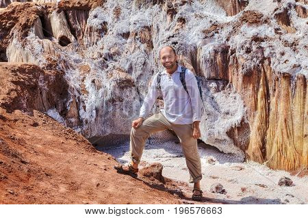 Smiling tourist posing for a photographer against the backdrop of glaciers from rock salt during a hiking trip to natural attractions Hormuz Island Hormozgan Province Southern Iran.