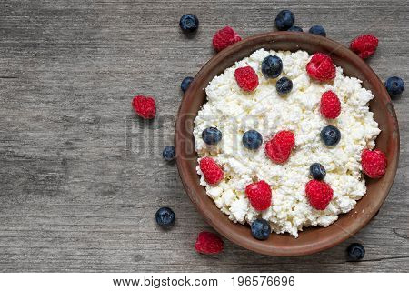 cottage cheese with fresh raspberries and blueberries in a bowl for healthy breakfast with ripe berries over rustic wooden background. top view