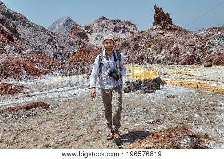 One smiling tourist Caucasian man walks by natural attractions with a camera Hormuz Island Hormozgan Province southern Iran.