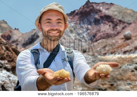 A smiling traveler holds out to the camera the palms on which large pieces of rock salt lie Hormuz Island Hormozgan Province southern Iran.