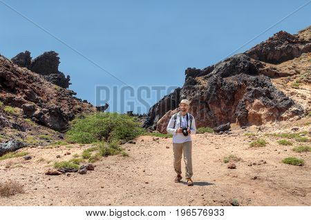 Iranian Island of Hormuz in Persian Gulf mature man tourist with a backpack and camera goes on mountain trail.