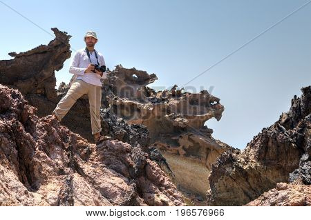 A tourist in a panama stands on a rock with a camera Hormuz Island Hormozgan Province southern Iran.