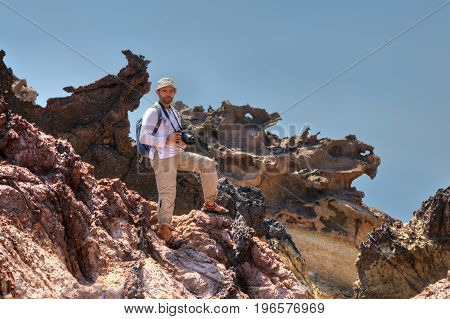 A traveler with a backpack and a camera stands on a rock Hormuz Island Hormozgan Province southern Iran.