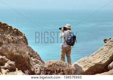 Photographer traveler in a panama on his head and a backpack behind his shoulders stands on the edge of a cliff over the sea Hormuz Island Hormozgan Province southern Iran.