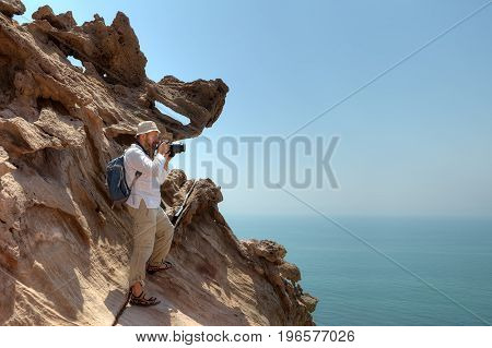 Photographer traveler stands on rock in Hormoz Island southern Iran.