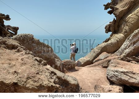 Tourist photographing nature standing on the edge of a cliff. Iranian Island of Hormuz in Persian Gulf Hormozgan Province southern Iran.