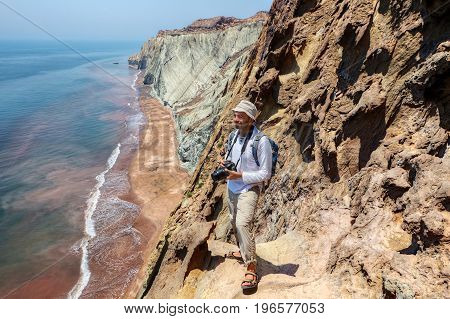 A happy tourist with a camera stands on the edge of a cliff Hormuz Island Hormozgan Province southern Iran.