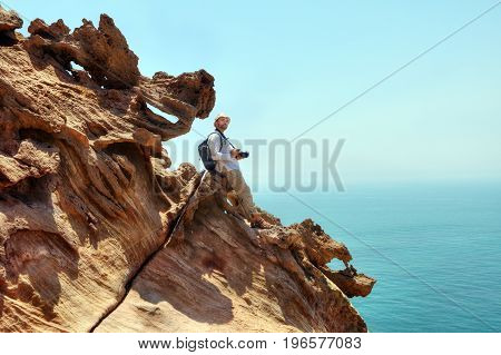 Nature photographer with a camera standing on the edge of the cliff above the sea Hormuz Island Hormozgan Province southern Iran.
