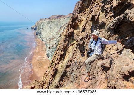 Happy photographer traveler sitting on the edge of a cliff Hormuz Island Hormozgan Province southern Iran.