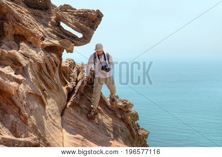 Photographer traveler climbs the cliff above the sea Hormuz Island Hormozgan Province Iran.