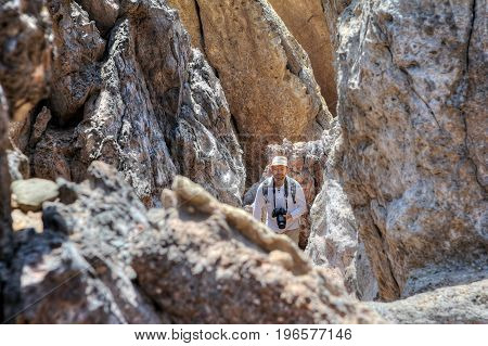 Smiling backpacker with a camera goes down the path between the rocks Hormuz Island Hormozgan Province Southern Iran.