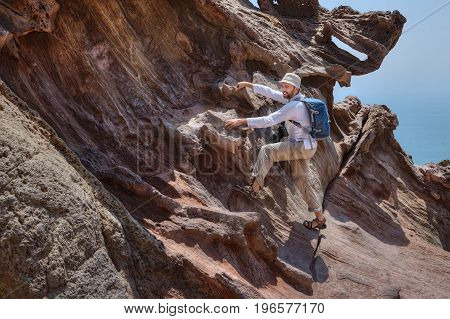 A traveler photographer climbs on a rock to photograph a beautiful natural view Hormuz Island Hormozgan Province Southern Iran.