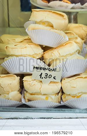 Pile of homemade baked meringues on a cake stand in display window of artisan bakery in a European city Spain