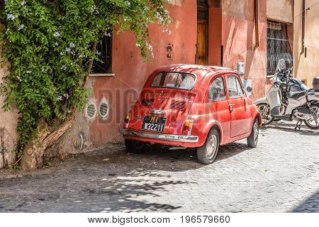 Rome Italy - August 20 2016: Red italian car parked in a picturesque street in Trastevere a sunny summer day in Rome