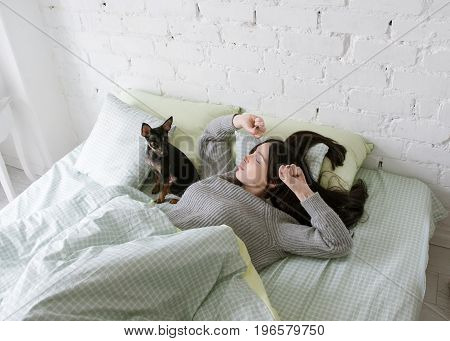 Lonely girl wake up with dog. Friendship with small puppy, single woman morning with pet
