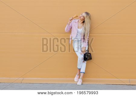 Beautiful cute funny amazing young hipster teen girl eating ice cream cone bright casual wear, orange background, urban style. Copy space
