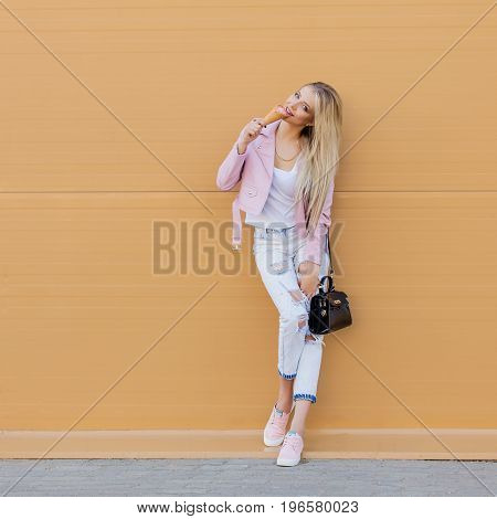Beautiful cute funny amazing young hipster teen girl eating ice cream cone, laughs happy, bright casual wear, orange background, urban style. Copy space