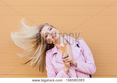 Beautiful cute funny amazing young hipster teen girl eating ice cream cone, laughs happy, bright casual wear, orange background, urban style. Flying hair. Copy space