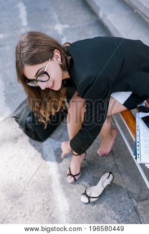 Confident and uninhibited girl taking off shoes. Young woman with tired legs, modern social behavior