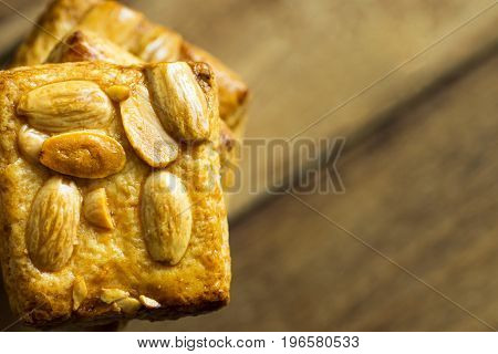 High stack of homemade almond Christmas cookies on plank wood background top view copy space side position frame holiday baking template