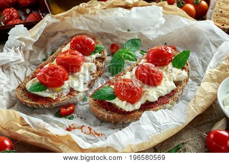 Tomato Ricotta Bruschetta with sun dried tomatoes paste, olive oil brown bread and basil.
