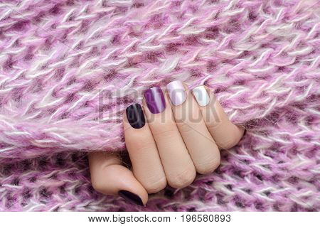 Purple nail design. Beautiful female hand with different shades of purple manicure.