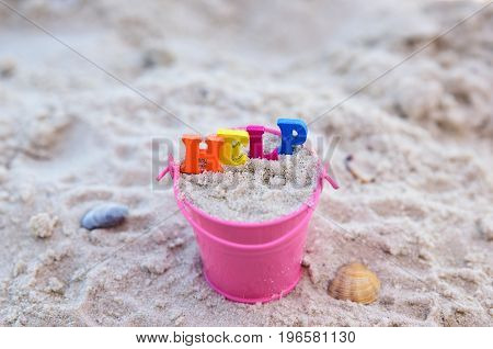 Word help from multicolored wooden letters in an iron pink bucket top view