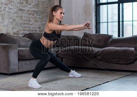 Beautiful fit girl doing home workout performing lateral lunges in a sitting room.