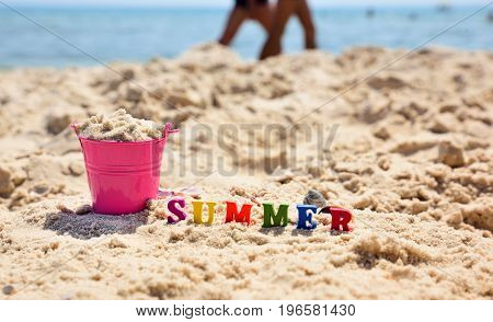 Inscription summer on the sand against the blue sea next to a full pink bucket of sand