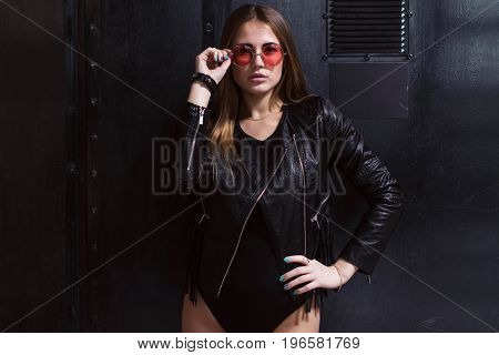 Stylish attractive female model in pink sunglasses, leather jacket and bodysuit standing over black background.