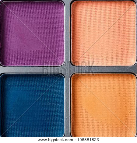 Set of blue, orange and purple eye shadows, the top view
