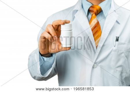 A Male Doctor In White Coat With A Stethoscope On Shoulder Holding a Bottle Of Pills Between His Fingers. Healthcare Medical Hospital Concept